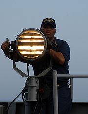 Navy seaman sending morse code signals